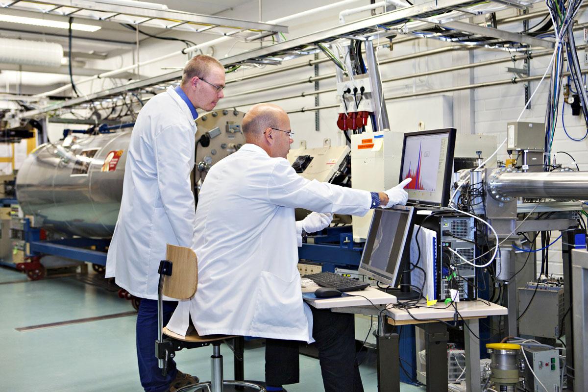 Tutkija Marko Käyhkö ja professori Timo Sajavaara tarkastelevat PIXE-mittauksen röntgenspektriä, jossa näkyvät eri alkuaineet kullekin luonteenomaisina piikkeinä. Taustalla protonisuihkun tuottamiseen käytettävä 1,7 miljoonan voltin hiukkaskiihdytin.