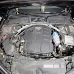 Moottori on Audin perinteiden mukaisesti pitkittäin. Konepellin etureunan tiivistehuuli ei pysty täysin estämään lian pääsyä sisään. Lasinpesunesteen sininen täyttöaukko oikeanpuoleisen A-pilarin juuressa on kätevä, jos käytössä on nokkakannu. Kanisterin kanssa tulee sotkua.