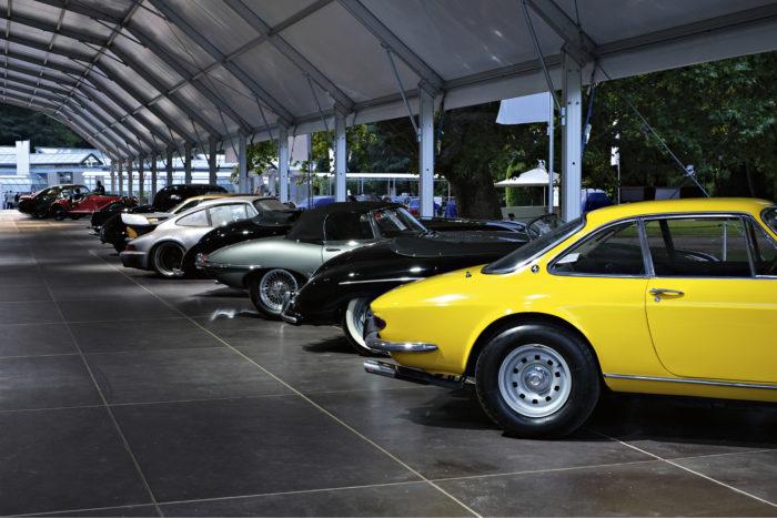 RM Sotheby'sin näyttelyhallin iltavalaistuksessa huutokaupasta palanneet Ferrarit, Porschet, Jaguarit ja muut klassikot odottavat uusia omistajia.