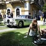 Elegantin piknikin ainekset koossa: Grand Hotel Villa d'Esten viiden tähden nurmikolla auringosta ja ohilipuvasta jalometallista nauttimassa. Kuvan auto on Lagonda Rapide vuosimallia 1962.